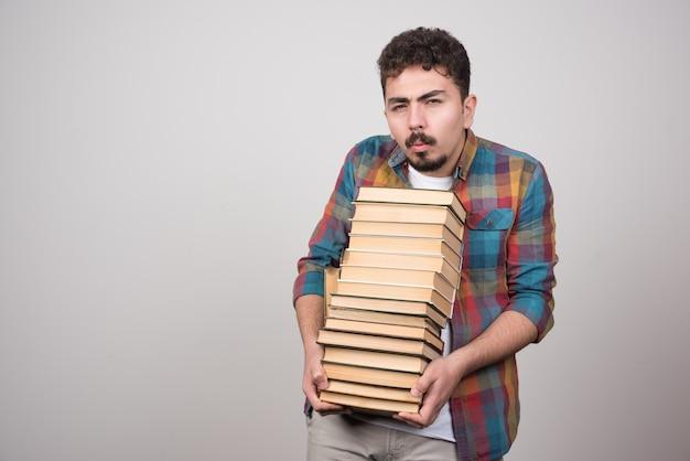Jonge mannelijke student die met stapel boeken camera bekijkt.
