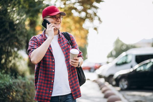 Jonge mannelijke student het drinken koffie die telefoon in park met behulp van