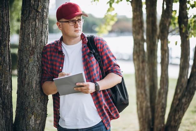 Jonge mannelijke student het drinken koffie in park