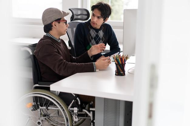Jonge mannelijke student in rolstoel die aan computer werkt