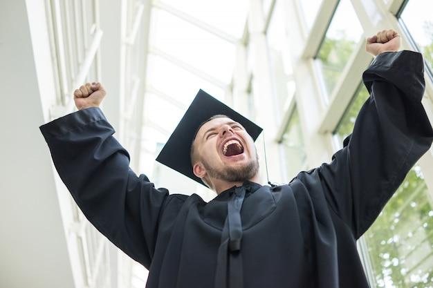 Jonge mannelijke student in zwarte afstuderen jurk