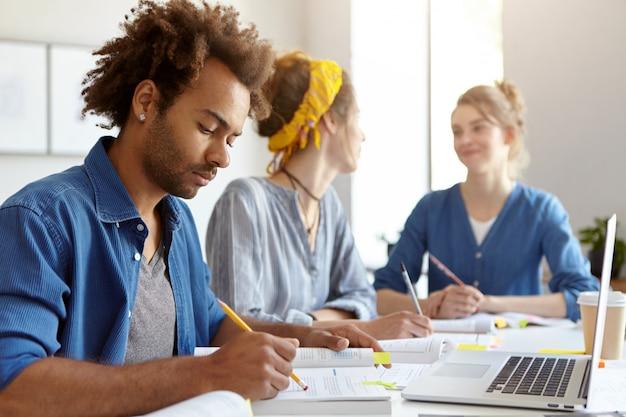 Jonge mannelijke student met afro-kapsel, aandachtig leesboek, zittend voor geopende laptop in klaslokaal en zijn twee vrouwelijke groepsgenoten die met elkaar babbelen. onderwijs en teamwork concept
