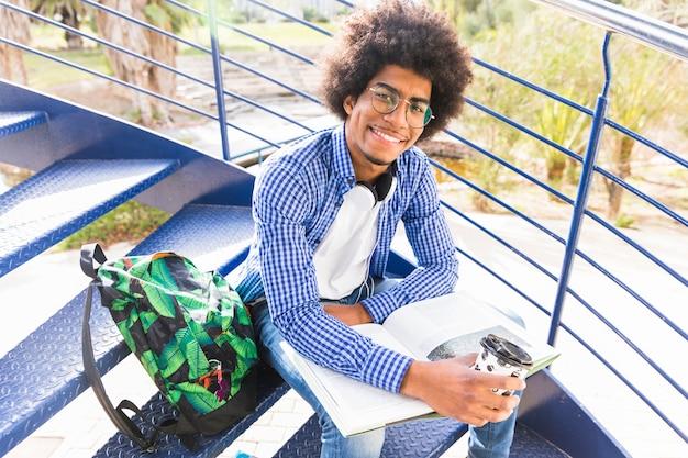 Jonge mannelijke studentenzitting op de trap met rugzak; boek en afhaal koffiekopje