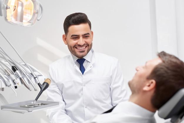 Jonge mannelijke tandarts die bij zijn patiënt glimlacht tijdens medische benoeming