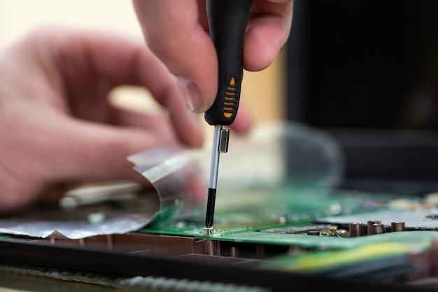 Jonge mannelijke tech of ingenieur repareert elektronische apparatuur in onderzoeksfaciliteit. een man demonteert een computer met een magnetische schroevendraaier