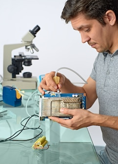 Jonge mannelijke tech reinigt defecte computerprocessor