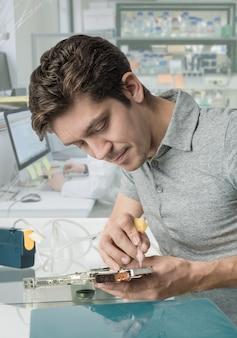 Jonge mannelijke tech werkt in onderzoeksfaciliteit