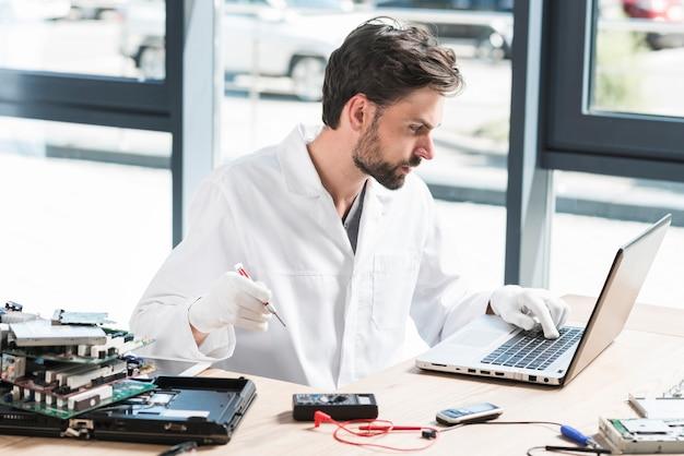 Jonge mannelijke technicus die laptop in workshop met behulp van