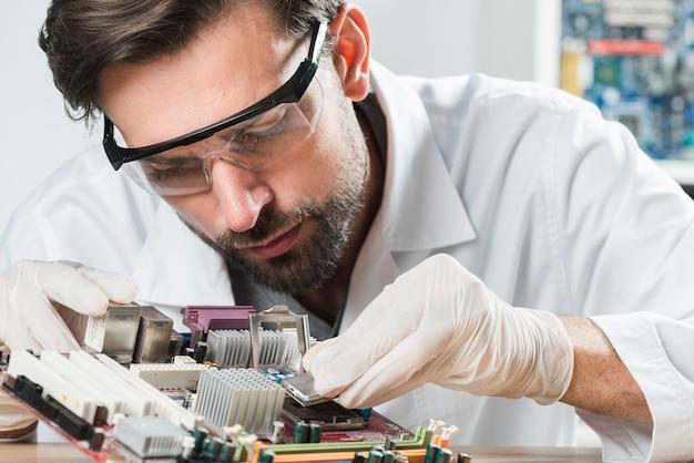 Jonge mannelijke technicus die veiligheidsbril draagt die spaander invoegt in computermotherboard