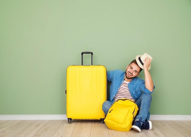 Jonge mannelijke toerist met bagage die dichtbij kleurenoppervlakte zit