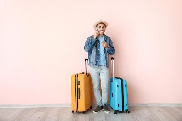 Jonge mannelijke toerist met bagage praten via de telefoon in de buurt van kleur oppervlak