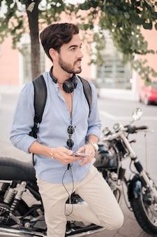 Jonge mannelijke toerist met smartphone die zich voor motor bevindt