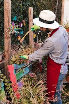 Jonge mannelijke tuinman die de installatie met slang water geeft