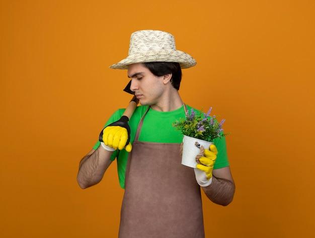 Jonge mannelijke tuinman in uniform dragen tuinieren hoed met handschoenen met gesloten ogen houden bloem in bloempot schop zetten schouder geïsoleerd op oranje