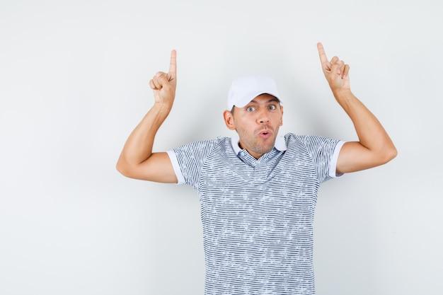 Jonge mannelijke vingers omhoog in t-shirt en pet en op zoek verontrust