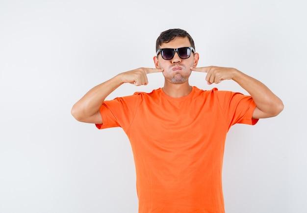 Jonge mannelijke vingers op geblazen wangen in oranje t-shirt te drukken en er grappig uit te zien