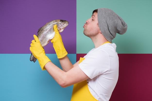 Jonge mannelijke visser met gele schort die een grote zalm, forelvis houdt die het probeert te kussen. ik hou van mijn werk.