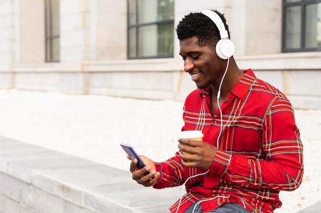 Jonge mannelijke volwassene die zijn mobiele telefoonwit gebruikt dat zijn koffie drinkt