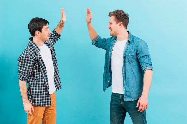 Jonge mannelijke vriend die hoogte vijf geeft tegen blauwe achtergrond