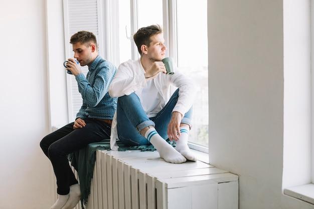 Jonge mannelijke vrienden die dichtbij venster zitten die ochtendkoffie hebben