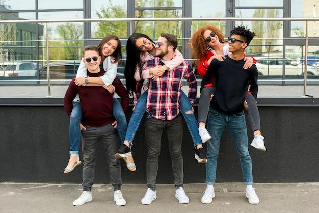 Jonge mannelijke vrienden die op de rug naar hun vrouwelijke vrienden vervoeren