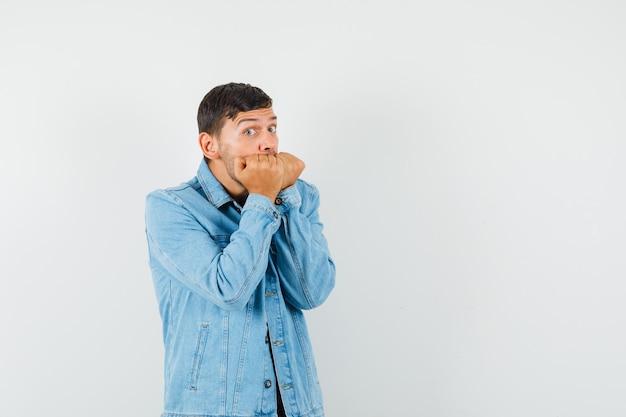 Jonge mannelijke vuisten emotioneel bijten in t-shirt jasje en op zoek doodsbang