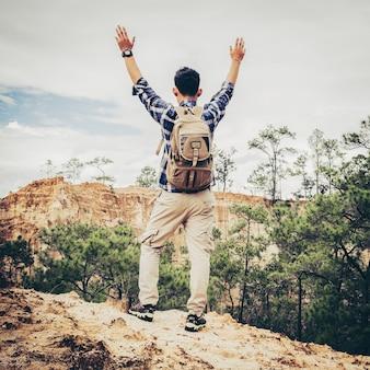Jonge mannelijke wandelaar met rugzak die bovenop de berg en opgewekte handen komt. man toerist staande op de rand van de prachtige canyon, overwinnende armen omhoog. achteraanzicht achteraan.