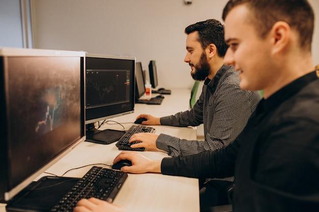 Jonge mannelijke webontwerpers die aan een computer werken