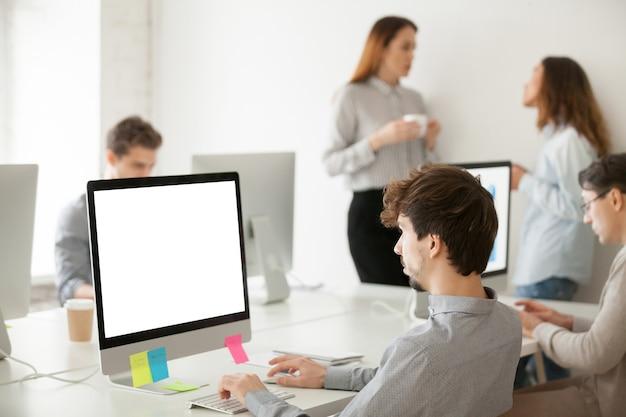 Jonge mannelijke werknemer die aan computer schrijven e-mail in bureau werkt