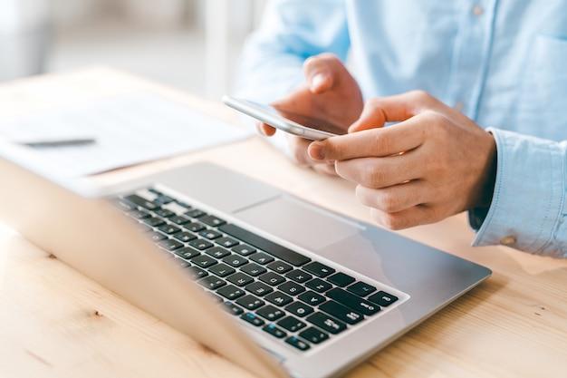 Jonge mannelijke werknemer scrollen of sms'en in smartphone via laptop toetsenbord zittend door houten tafel
