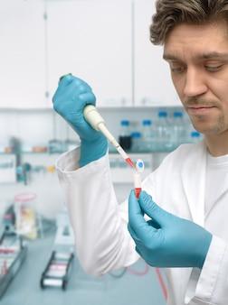 Jonge mannelijke wetenschapper of afgestudeerde student met pipet