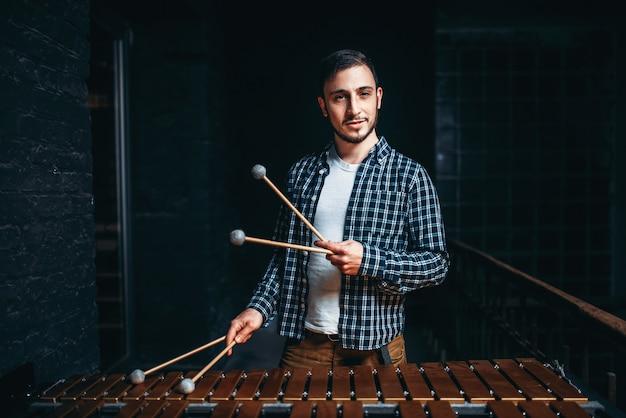 Jonge mannelijke xylofonist met stokken in handen
