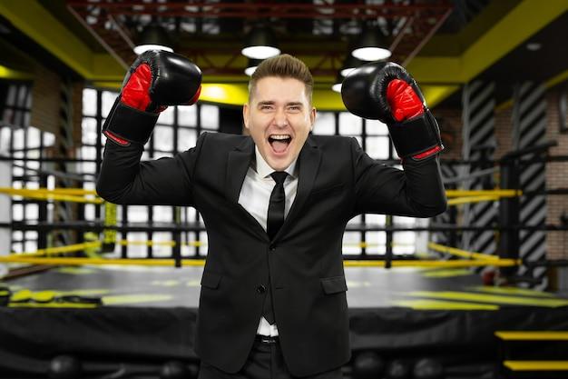 Jonge mannelijke zakenman in een pak en bokshandschoenen heeft plezier en lacht.