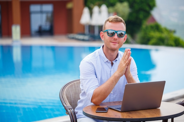 Jonge mannelijke zakenman in zonnebril werkt op een laptop zittend aan een tafel bij het zwembad. afstandswerk. freelancer