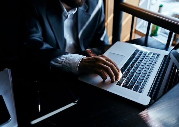 Jonge mannelijke zakenman zit aan een tafel met papieren en drinkt koffie, kijkt uit het raam
