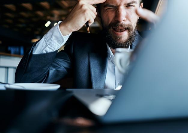 Jonge mannelijke zakenman zit aan een tafel met papieren en koffie drinkt, kijkt uit het raam