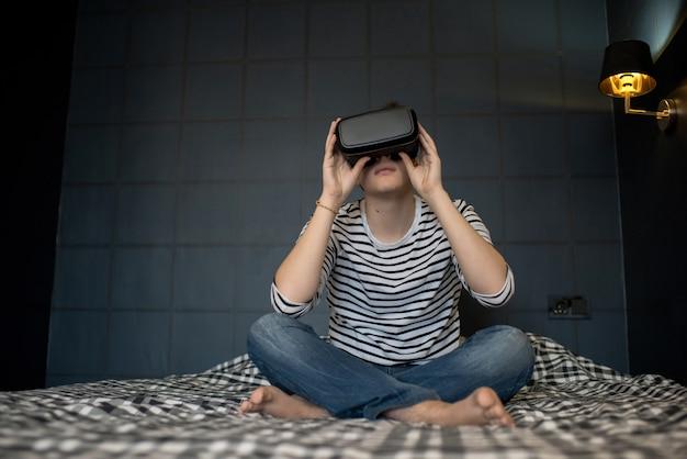 Jonge mannelijke zittend op bed met vrã 'headset