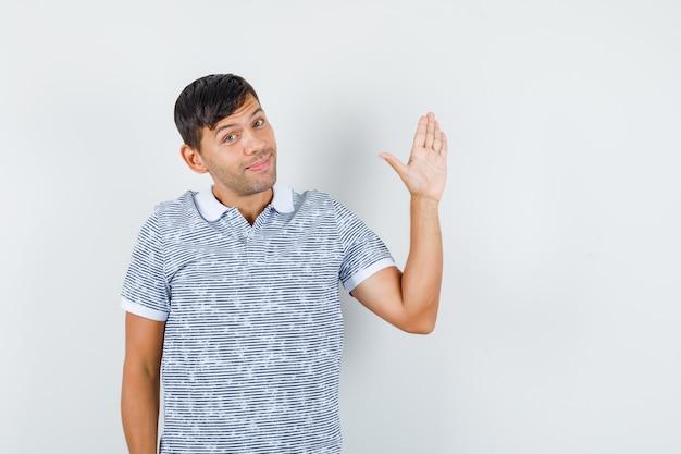 Jonge mannelijke zwaaiende hand om afscheid te nemen in t-shirt en op zoek blij