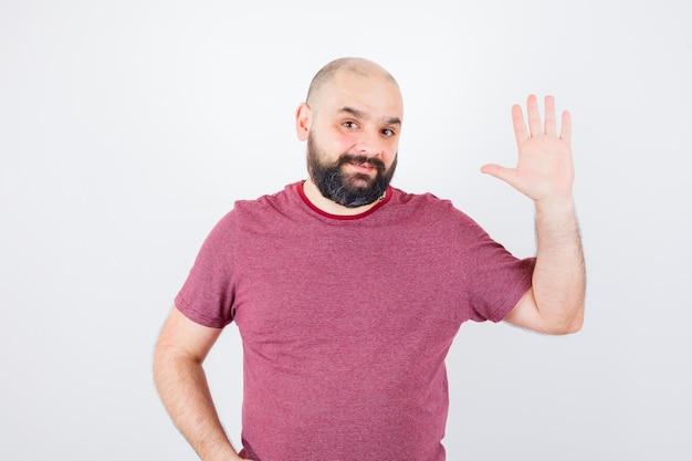 Jonge mannelijke zwaaiende hand voor groet in roze t-shirt, vooraanzicht.