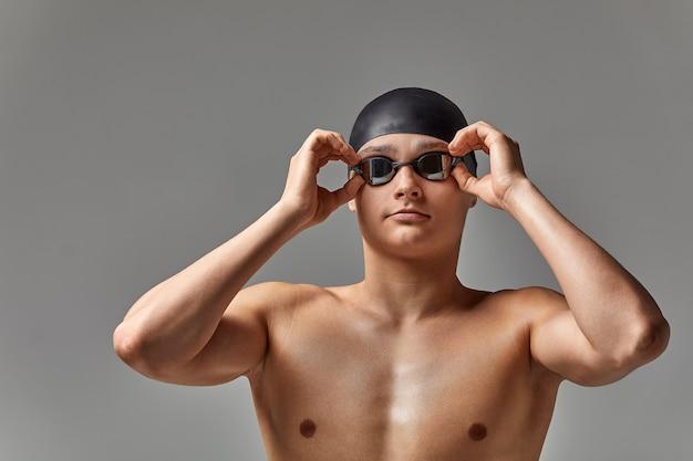 Jonge mannelijke zwemmer die zich voorbereidt op de start, close-up portret van een zwemmer in een masker en een hoed, grijze achtergrond, kopieerruimte, zwemconcept.