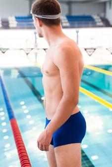 Jonge mannelijke zwemmer klaar om te zwemmen