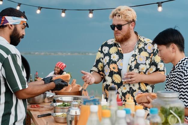 Jonge mannen brengen tijd buiten op het strand door en kopen hotdogs voor de lunch