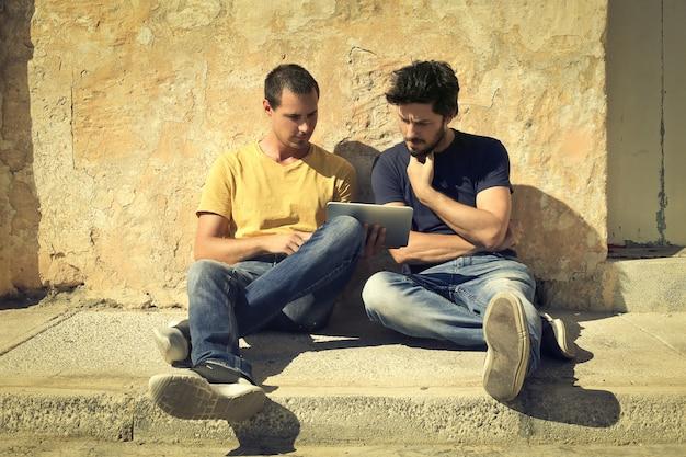 Jonge mannen die een tablet op straat gebruiken