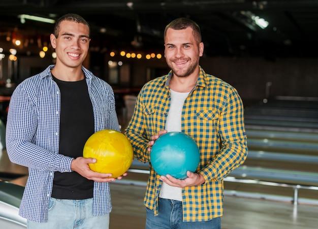 Jonge mannen die kleurrijke kegelenballen houden
