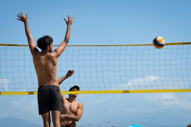 Jonge mannen die op een zonnige dag beachvolleybal spelen op het strand
