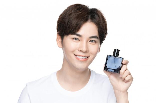 Jonge mannen die parfum spuiten