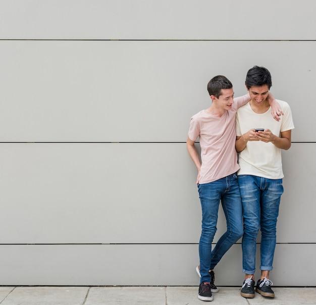 Jonge mannen die samen een telefoon doorbladeren