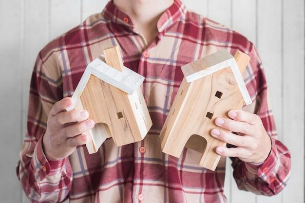 Jonge mannen dragen rode gingham shirt houden miniatuur huis model, onroerend goed investeringen concept