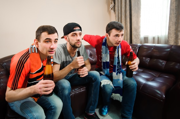 Jonge mannen drinken bier, eten chips en rooten voor voetbal