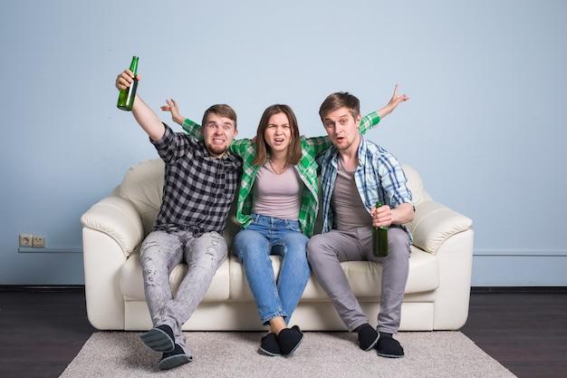 Jonge mannen drinken bier, eten pizza en juichen voor voetbal